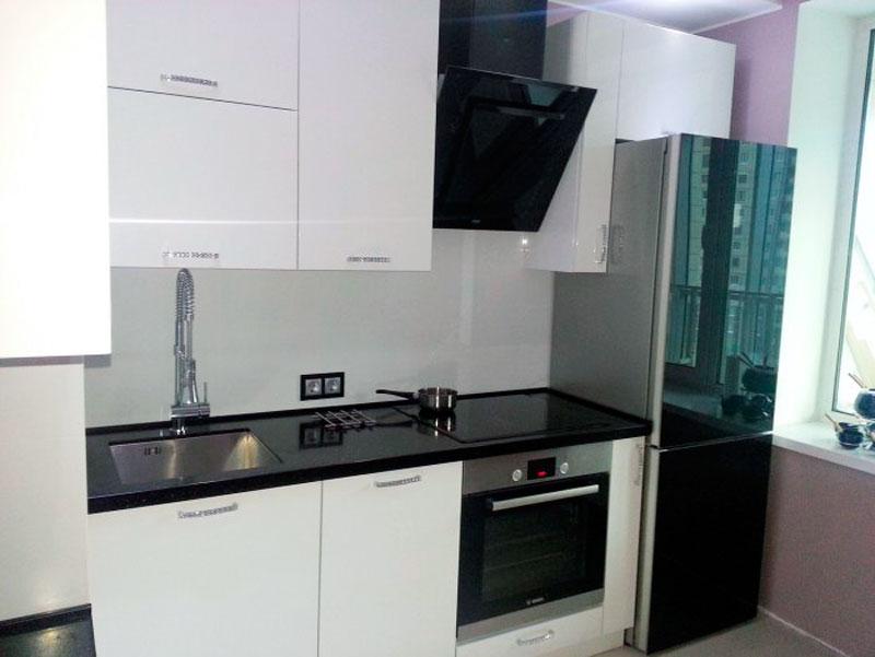 Дизайн фартука в черно-белой кухне площадью 7,5 м2, сделанной в стиле модернизма. За счет использования белой затирки, швов практически невидно.