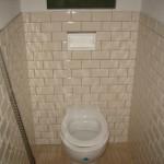 Стены в туалете облицованы наполовину бежевым кабанчиком