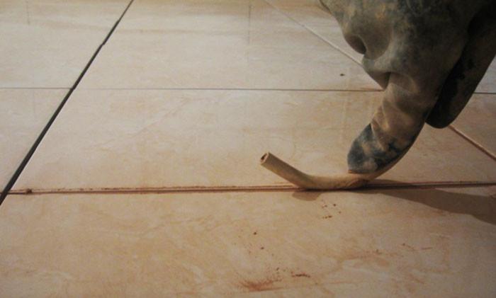 Пальцем либо специальным, входящим в комплект, цилиндрическим шпателем аккуратно пройдитесь по затирке и снимите небольшой верхний слой – это служит декоративным целям и уплотняет смесь. Если в комплекте нет круглого шпателя, его можно заменить проводом сечением 8—10 мм.