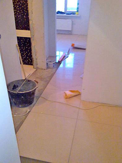 Глянцевый керамогранит 60х60 см в узком коридоре. При такой раскладке будет некрасивая подрезка вдоль всей стены. В таком помещении лучше выбрать плитку меньшего формата. Глянцевая поверхность очень скользкая, особенно по мокрому полу.