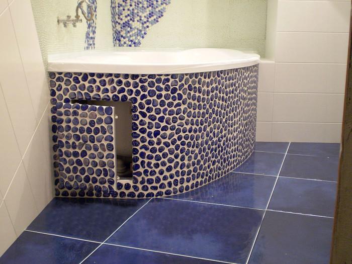 Облицовка экрана округлой ванны красивой мозаикой под камень.