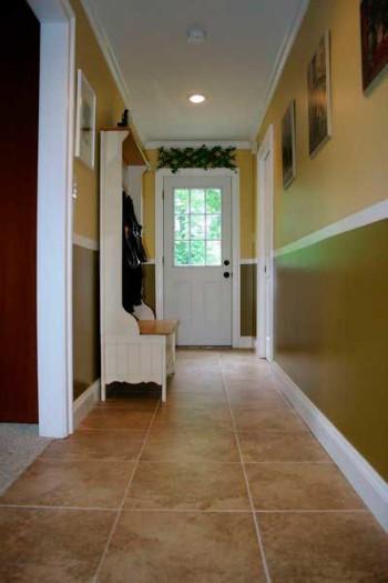 Стандартная плитка под камень отлично гармонирует с жёлто-зелёными стенами. Раскладка расположена равномерно от центра, поэтому крайние подрезки не выделяются.