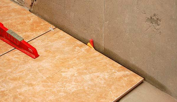 Чтобы между плитами формировались одинаковые швы, используйте плиточные крестики. По причине недостаточной калибровки кафеля, возможно, придётся прибегнуть к помощи пластиковых клиньев – они помогают точнее корректировать швы. Также они подходят для создания небольшого зазора у стены.