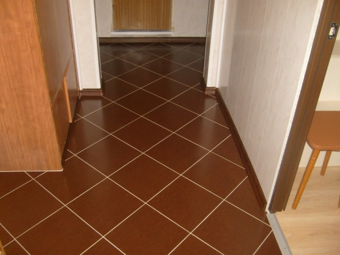 Квадратная коричневая плитка уложена по диагонали.