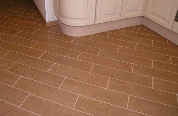 Плитка под дерево уложена по диагонали со смещением на кухне и в коридоре без перехода.
