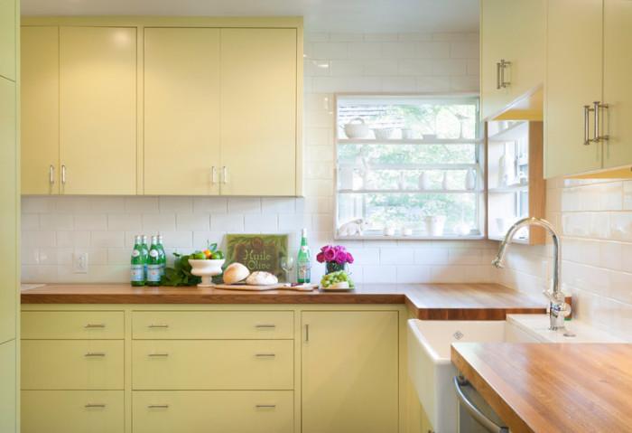Пастельно-зелёная мебель с деревянными столешницами выделяется на фоне простой белой плитки под кирпичик.