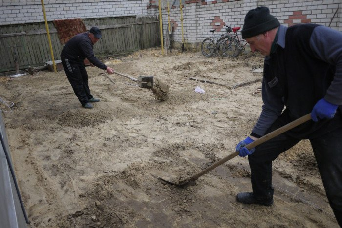 Выровняйте основание относительно шнура. Где грунт сильно выступает, снимите её, а где есть ямы — подсыпьте.