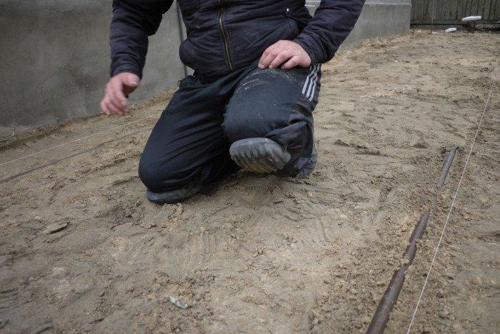 Надеваем старую обувь и наколенники. Становимся на колени в мини-прямоугольник и проводим правилом под нитью, чтобы увидеть, где нужно добавить цементно-песчаной смеси. Подсыпаем и утрамбовываем до получения ровного основания.