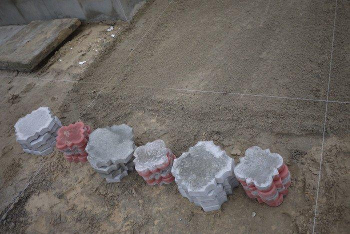 Складываем плитку стопками рядом с местом укладки и заодно осматриваем её. Дефектную и кривую плитку лучше отложить в сторону и не использовать.