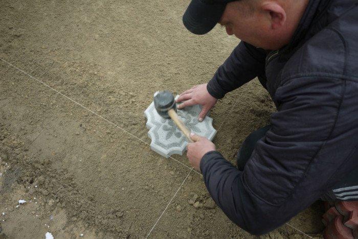 Укладываем первую плитку в угол и совмещаем её по осям с нитью.