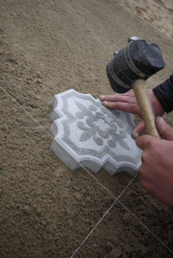 Простукиваем плитку резиновым молотком, чтобы утопить до уровня разметки.