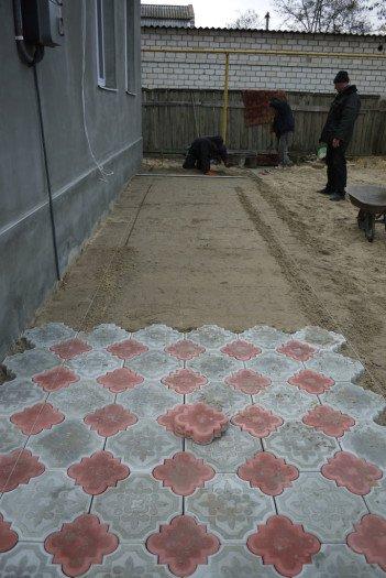 Продолжаем поэтапно укладывать плитку. Сначала один прямоугольник, затем соседний и так далее. Контролируем уровень дорожки правилом относительно натянутых нитей.