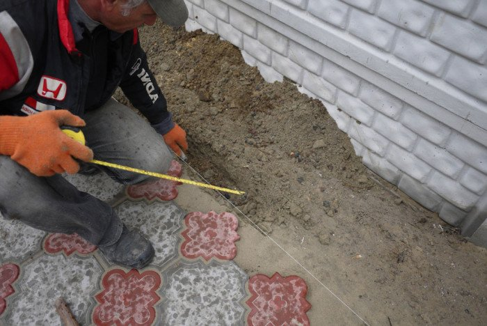 Для этого вдоль кромки мастерком или лопаткой прокопайте траншею.