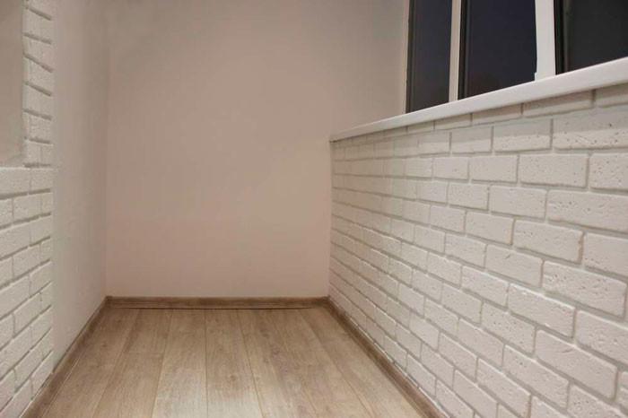 Оформление стен на балконе белой гипсовой плиткой под кирпич.