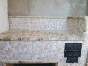 Печь-лежанка отделана шамотной плиткой.